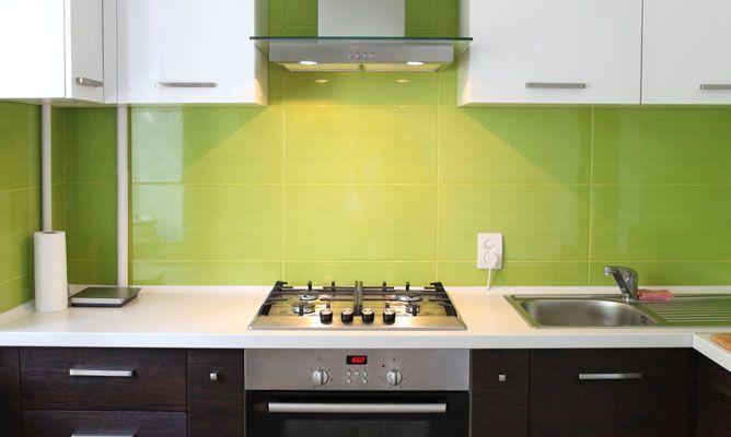 cocina con cerámicas verde y gabinetes blancos