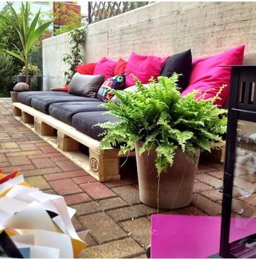 Un sofá bajo hecho de palets, decorado con cojines de varios colores