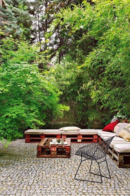 Un salón de jardín con un gran sofá esquinero y una mesa de centro de palets con aspecto envejecido