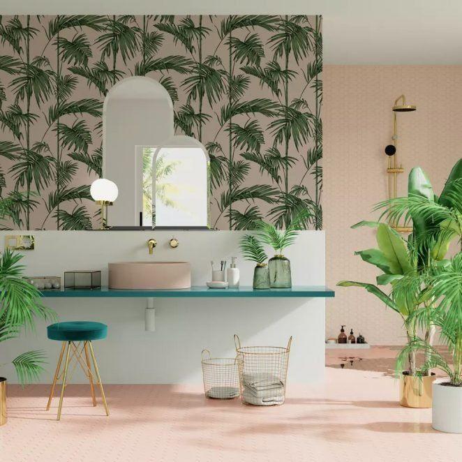 Un baño con papel pintado tropical y azulejos rosas invita a viajar