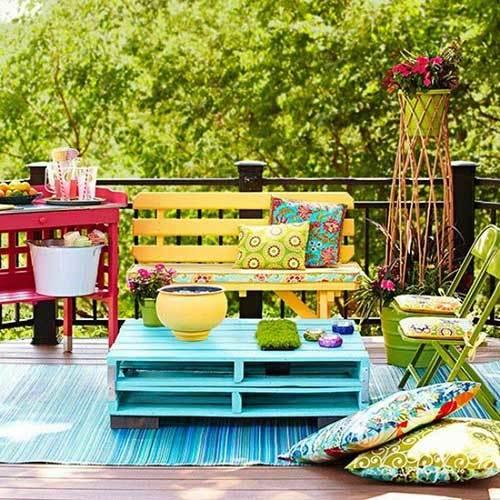 Un colorido mobiliario de jardín en la terraza con cada mueble pintado de un color diferente