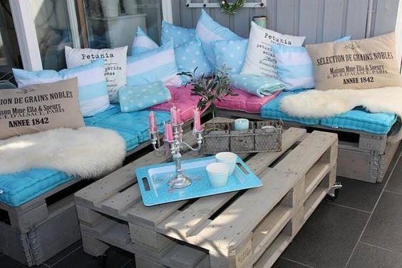 Un pequeño mueble de jardín, compuesto por una mesa de centro y un sofá de esquina con muchos cojines para mayor comodidad