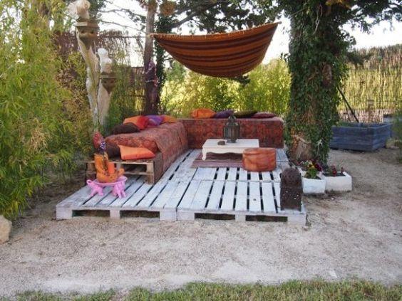 Los palets se utilizan aquí para hacer una plataforma para crear un salón de jardín con un ambiente bohemio