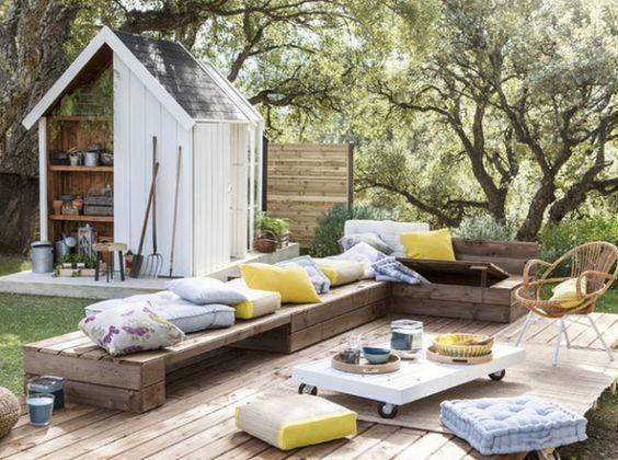 Un salón de jardín hecho de palets con acogedores y coloridos cojines