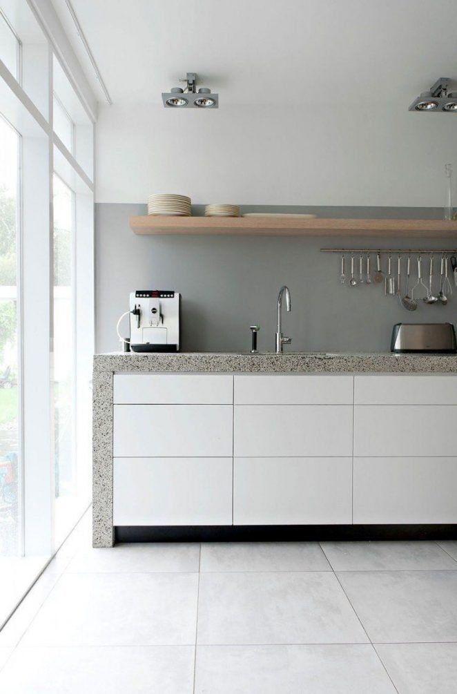 El gris se combina en esta cocina con el terrazo, la madera rubia y los muebles blancos con elegancia