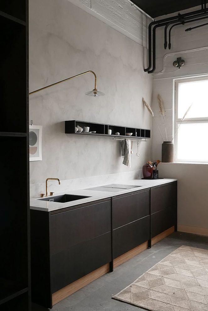 Clase absoluta para esta cocina de líneas escandinavas cuya pared principal está pintada en gris ratón