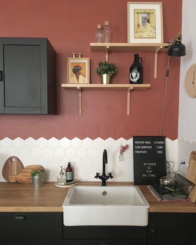 Los muebles negros y las estanterías de madera rubia combinan bien con la pintura terracota de la cocina